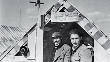 "[Picture: Republican refugees standing under a sign saying ""Gran-Hotel Euzkeldun no. 95"" at an internment camp for Spanish exiles, Le Barcarès, France. The Robert Capa and Cornell Capa Archive, 2014]"