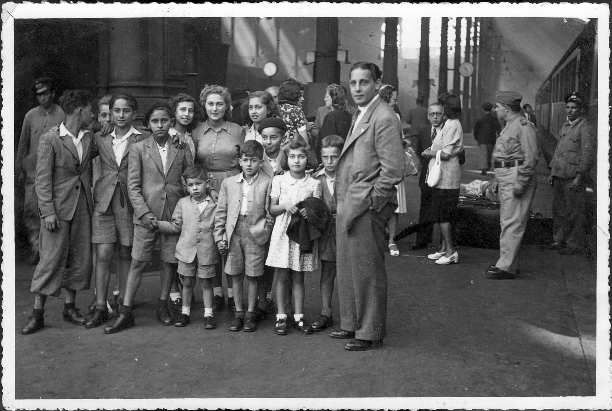 Grup de nens a l'estació de ferrocarril de Lisboa l'agost de 1944 després d'arribar des de Barcelona. Havien creuat clandestinament els Pirineus. Els acompanya Joel Sequerra, representant del American Jewish Joint Distribution Committee | Yad Vashem