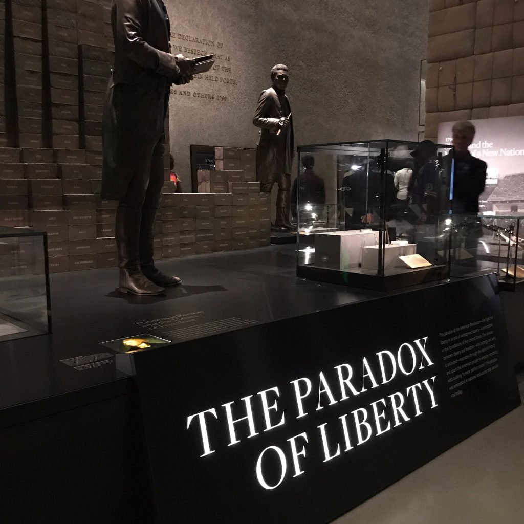 A statue of Thomas Jefferson hovers over the illuminated phrase, while a black figure hovers in the background.
